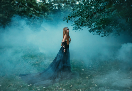 Photo for The dark queen of elves walks in a misty forest. A creative image, an unusual black dress. Artistic toning. - Royalty Free Image
