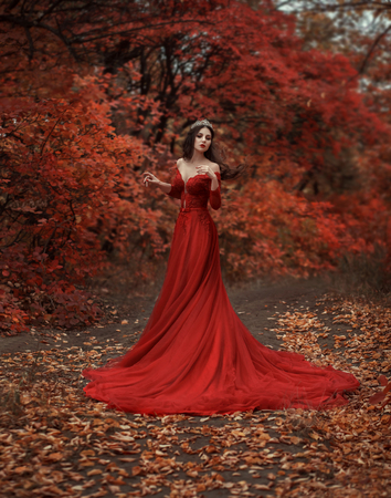 Photo for Incredible stunning girl in a red dress. The background is fantastic autumn. Artistic photography. - Royalty Free Image