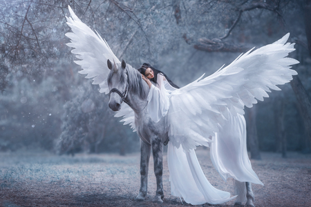Photo pour Beautiful, young elf, walking with a unicorn. She is wearing an incredible light, white dress. The girl lies on the horse. Sleeping Beauty. Artistic Photography - image libre de droit