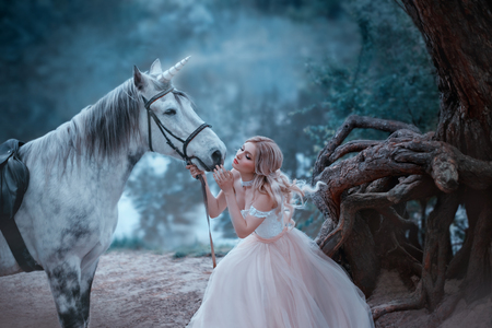 Photo for A fairy in a tender vintage dress hugs a unicorn. Fantastic magical, radiant horse. Background river and forest. Blonde girl with wavy hair - light elf. Artistic Photo - Royalty Free Image