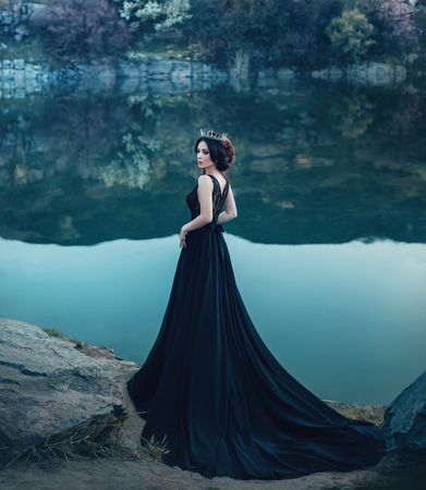 Photo pour A majestic lady, a dark queen, stands on the background of a river and rocks, in a long black dress. The brunette girl in the gothic crown. Gloomy tone, artistic retouching - image libre de droit