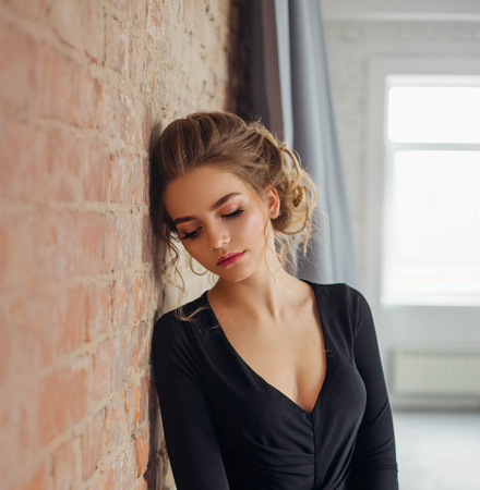 Photo pour A young blonde girl in a strict, discreet, modest, elegant, long black dress. Delicate natural make-up. Beautiful, elegant, high hairstyle for an average length of hair, with weaving. Evening image - image libre de droit