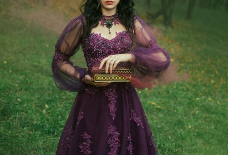 Foto de a dark-haired young lady holds in her hands an open Pandoras box, the red maroon thick fog of evil and disease slowly comes out, as a punishment for humanity. gothic image, art photo without a face - Imagen libre de derechos