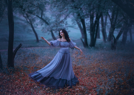 Photo pour a mysterious girl with wavy dark hair is dancing alone on fallen autumn leaves in a gloomy night forest in a long wonderful blue vintage dress, fabulous heroine, knows no ills, the legend of Pandora - image libre de droit