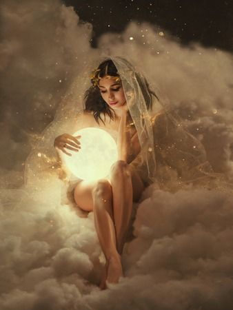 Photo pour gorgeous slender sexy lady sits in the clouds and holds the moon in her hands. daughter of the sun and sky, keeper of dreams, ready to do good and a fairy tale under the cover of night and the stars - image libre de droit