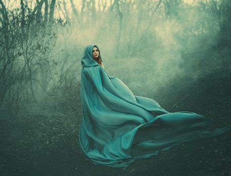 Photo pour attractive large lady in long blue summer light waving raincoat runs through forest with bare trees and mysterious white smoke and magical fog, charming sorceress escapes from a fairytale monster - image libre de droit