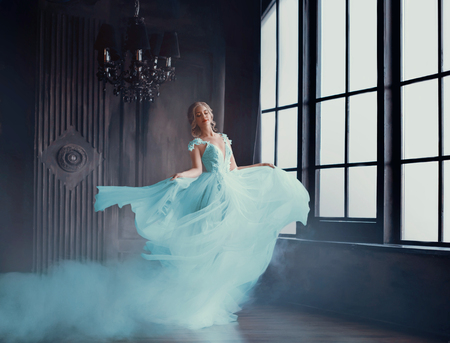 Photo pour The magical transformation of Cinderella into a beautiful princess in a luxurious dress. Young women are blonde, spinning and dancing in a dark, gloomy room, the dress fluttering on the fly. Art photo - image libre de droit