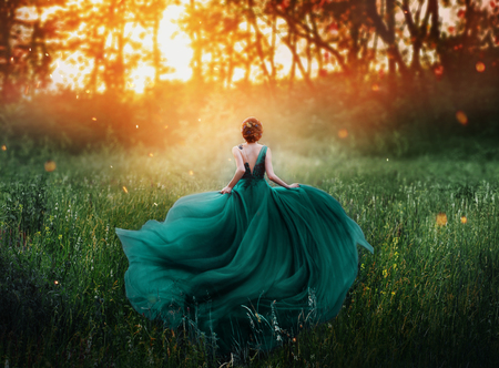 Photo for magical picture, girl with red hair runs into dark mysterious forest, lady in long elegant royal expensive emerald green turquoise dress with flying train, amazing transformation during fiery sunset. - Royalty Free Image