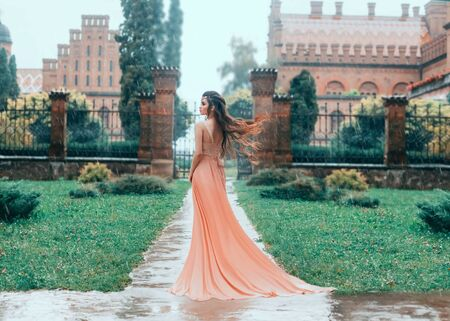 Photo for Lonely Attractive brunette woman walks in the rain near the stator castle. Young princess in a pink wet dress with a train. Hair fluttering, flying in the wind. Autumn sad landscape. - Royalty Free Image