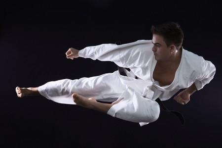 karate man champion of the world on black background studio shot