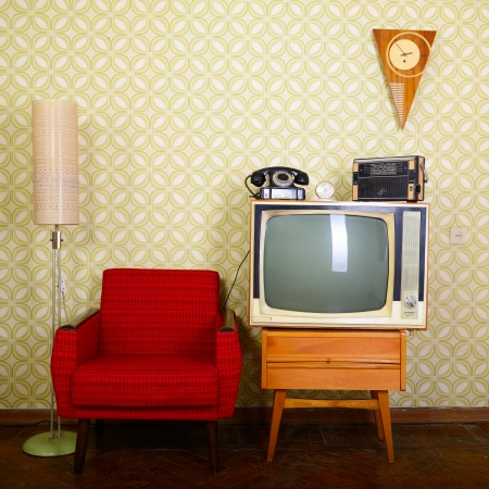 Vintage room with wallpaper, old fashioned armchair, retro tv, phone, clocks, radio player and standart lamp