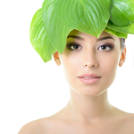 Foto de beautiful young cheerful woman with green leaves near her face, care of nature concept, over white background - Imagen libre de derechos