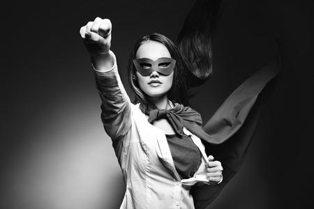 Foto de Young pretty woman opening her shirt like a superhero. Super girl, image toned. Beauty saves the world. Black and white. - Imagen libre de derechos