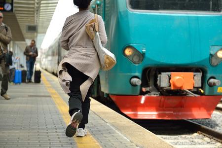 Photo pour Running woman miss train in railway station.  - image libre de droit