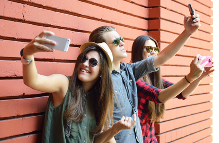 Foto de Young people having fun outdoor and making selfie with smart phone against red brick wall. Urban lifestyle, happiness, joy, friends, self photo social network concept. Image toned and noise added. - Imagen libre de derechos