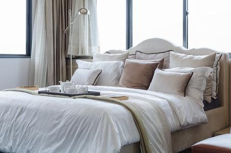 Photo pour tea cup set on classic bed with pillows at home - image libre de droit