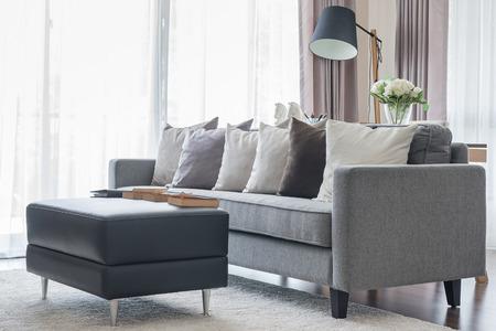 Foto de modern grey sofa with pillows and black table in living room at home - Imagen libre de derechos