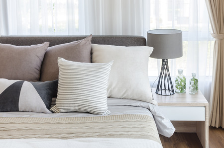 Photo pour modern style bedroom with pillows on bed and modern grey lamp on side table at home - image libre de droit