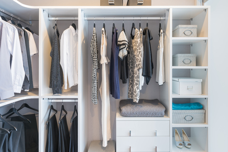 Photo pour clothes hanging on rail in white wardrobe with box and shoes - image libre de droit