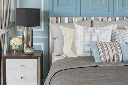 classic lamp style on wooden table in blue bedroom with classic bed and pillows