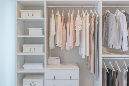 Foto de clothes hanging on rail in white wardrobe with boxes - Imagen libre de derechos