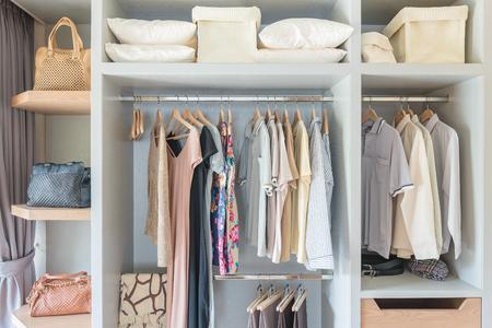 Foto de clothes hanging on rail in wooden closet at home - Imagen libre de derechos