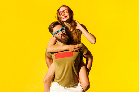 Photo for Piggyback. Happiness friend looking at camera and posing on yellow background. Studio shot - Royalty Free Image