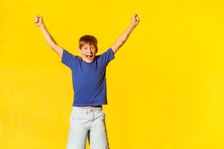 Photo for Yay! The happiness beautiful boy in casual clothing, looking at camera, celebrates the victory. Isolated studio shot on yellow background - Royalty Free Image