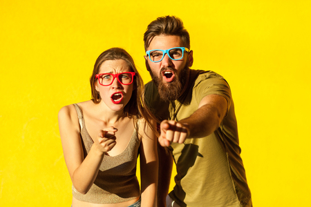 Foto de Hey you! Young adult bearded man, and cute brunette pointing fingers and looking at camera. On yellow background. Indoor, studio shot - Imagen libre de derechos