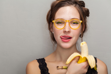Photo pour portrait of seductive woman in glasses holding banana and showing tongue out while looking at camera. indoor, studio shot on gray background. - image libre de droit