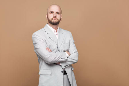 Photo pour Portrait of confused handsome middle aged bald bearded businessman in classic light gray suit standing and thinking with crossed hands. indoor studio shot, isolated on light brown background. - image libre de droit