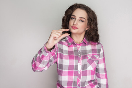 Foto per A little bit. pleased beautiful girl with pink checkered shirt, curly hairstyle and makeup standing, looking at camera and showing a few gesture. indoor studio shot, isolated on gray background. - Immagine Royalty Free