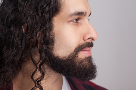 Foto de Closeup profile side view of handsome confident man with black long curly hair and beard, looking away with smile. male healthcare and beauty concept. indoor studio shot, isolated on gray background. - Imagen libre de derechos