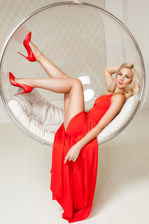 Foto de Sensual gorgeous fashionable blonde young woman in bright evening red dress with makeup and curly hairstyle lying and posing in hanged bubble chair, looking at camera with smile. indoor studio shot. - Imagen libre de derechos
