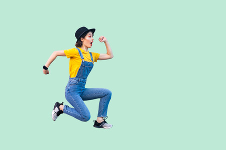 Foto per Profile side view portrait of surprised funny young hipster girl in blue denim overalls, yellow shirt and black hat jumping in super mario style. indoor studio shot isolated on light green background. - Immagine Royalty Free