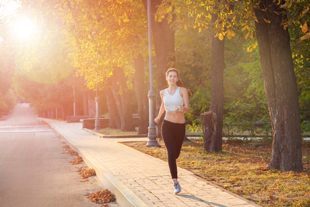 Photo pour young beautiful happy and sexy runner girl with nice body in the autumnal colored park. with sun on backlight is looking at camera with happiness and smile with white sport suit. - image libre de droit