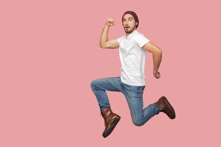 Foto de Portrait of carefree bearded hipster young man in white shirt and blue jeans with hat jumping and looking at camera with funny face. indoor studio shot, isolated on pink background - Imagen libre de derechos