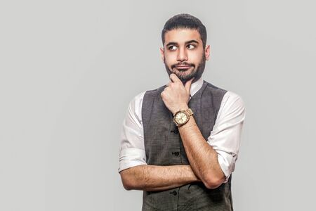 Photo pour Portrait of thoughtful or confused handsome bearded brunette man in white shirt and waistcoat standing, holding his chin, looking away and thinking. indoor studio shot isolated on gray background. - image libre de droit