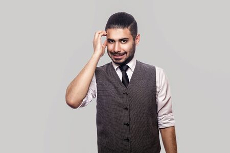 Photo pour Portrait of thoughtful handsome bearded brunette man in white shirt, waistcoat standing scratching his head, looking at camera and thinking what to do. indoor studio shot isolated on gray background. - image libre de droit