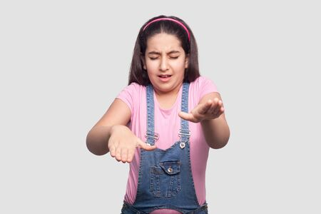 Photo for Portrait of closed eyes blind brunette young girl in casual pink t-shirt and blue denim overalls standing and try to touch or find something . indoor studio shot, isolated on light gray background. - Royalty Free Image