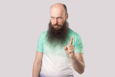Foto de Portrait of serious bossy middle aged bald man with long beard in light green t-shirt standing with warning gesture and looking at camera and alarming. indoor studio shot, isolated on grey background - Imagen libre de derechos