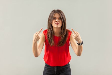 Photo pour Portrait of crazy angry brunette young woman in red shirt standing with middle finger fuck sign and looking at camera with anger face. indoor, studio shot, isolated on gray background. - image libre de droit