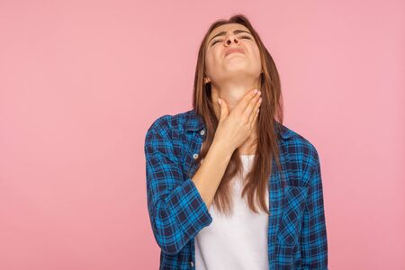Foto de Throat pain. Portrait of flu sick girl in checkered shirt touching her inflamed throat and grimacing from pain, suffering tonsillitis, thyroid disorders. indoor studio shot isolated on pink background - Imagen libre de derechos