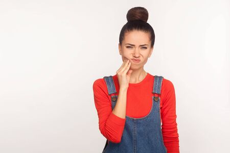 Foto de Portrait of unhealthy girl with hair bun in denim overalls touching sore cheek, suffering toothache, cavities or gum disease. indoor studio shot isolated on white background - Imagen libre de derechos