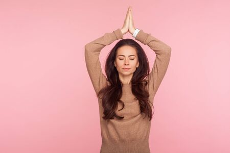 Photo pour Meditation, mind balance. Portrait of peaceful concentrated young woman with brunette wavy hair holding hands in namaste gesture over head, doing yoga. indoor studio shot isolated on pink background - image libre de droit