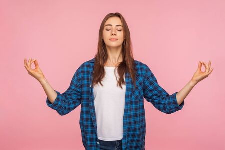 Photo pour Calm positive girl in checkered shirt holding hands in mudra gesture and meditating, practicing pranayama yoga, feeling harmony and inner balance. indoor studio shot isolated on pink background - image libre de droit