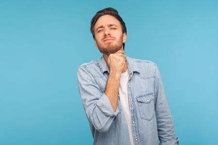 Foto de Portrait of flu-sick man in denim shirt clasping neck feeling unwell, suffering sore throat and inflamed tonsils, unbearable pain difficult to swallow. indoor studio shot isolated on blue background - Imagen libre de derechos