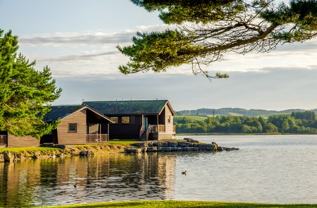 Photo pour A peaceful scene of wooden holiday lodges bwside a still lake - image libre de droit