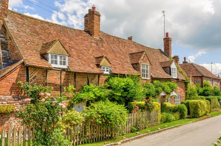 Foto de Gardens in front of row of cottages in the village of Turville, Buckinghamshire, England with blue skies. - Imagen libre de derechos