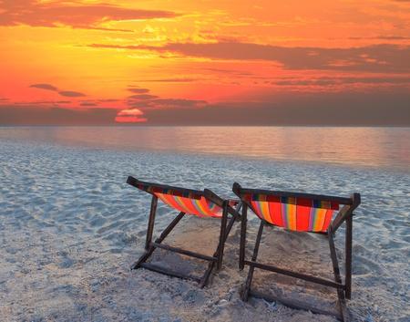 Photo pour couples chairs beach on sand beach with colorful sky - image libre de droit